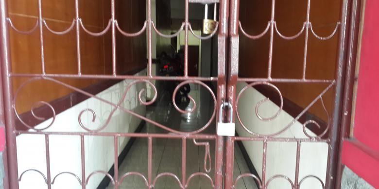 Pagar rumah kos Deudeuh Alfi Sahrin (26) di 15 C Tebet Timur, Jakarta Selatan, dipasangi gembok, Senin (20/4/2015). Pemasangan gembok di pagar tersebut guna memperketat penjagaan agara warga tidak lagi keluar masuk rumah kos yang bertingkat lima tersebut.