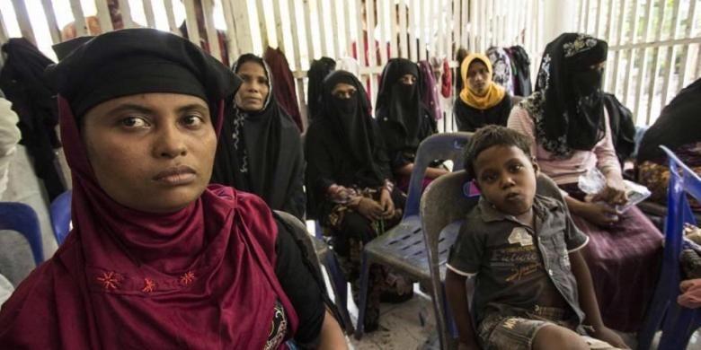 Wanita dan anak-anak imigran asal Myanmar dan Bangladesh menunggu di tenda darurat di Desa Matang Raya, Baktya, Aceh Utara, 10 Mei 2015. Sebanyak 469 orang asal Myanmar dan Bangladesh ditemukan terdampar di perairan utara Aceh.