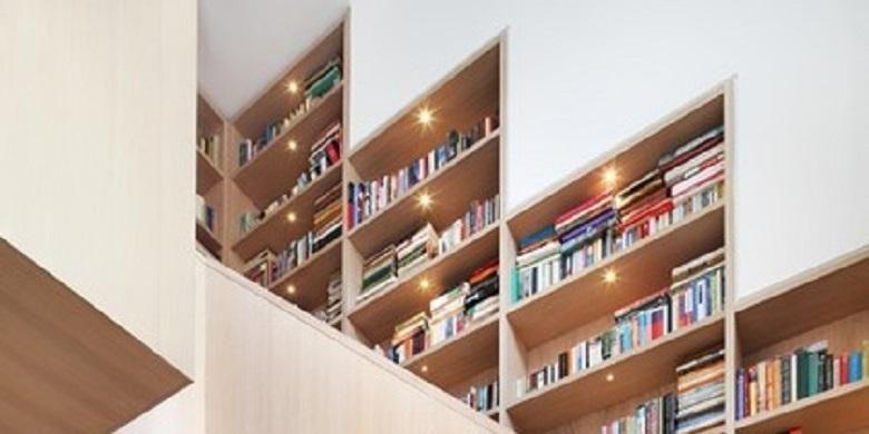 Tidak ingin rak-rak buku Anda mendominasi ruangan? Anda bisa membuat rak-rak sendiri sepanjang tembok di sisi tangga.