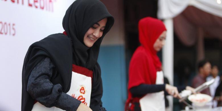 Umi Pipik (kiri) dan artis Annisa Trihapsari memasak mi goreng untuk berbuka puasa dalam acara Gerakan Ibu Memberi Lebih di Panti Asuhan Muhammadiyah, Tanah Abang, Jakarta, Rabu (24/6/2015). Pada 5 Juli mendatang, kegiatan yang sama juga akan dilakukan secara serentak oleh para ibu di 30 kota di Pulau Jawa untuk memasak menu buka puasa kepada anak-anak panti asuhan.