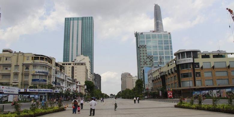 Plaza di kota Ho Chi Minh yang diapit gedung-gedung komersial perkantoran dengan latar belakang Bitexco Financial Tower.