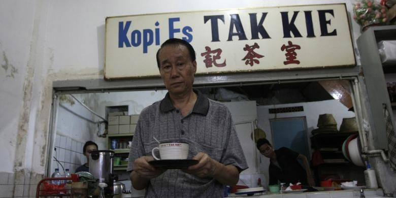 Pemilik kedai kopi es Tak Kie, Latif Yunus Membawa secangkir kopi di kedainya di kawasan Glodok, Jakarta Barat, Jumat (2/5/2014). Kedai kopi tua ini dirintis oleh Liong Kwie Tjong, kakek dari Latif Yunus sejak 1927.
