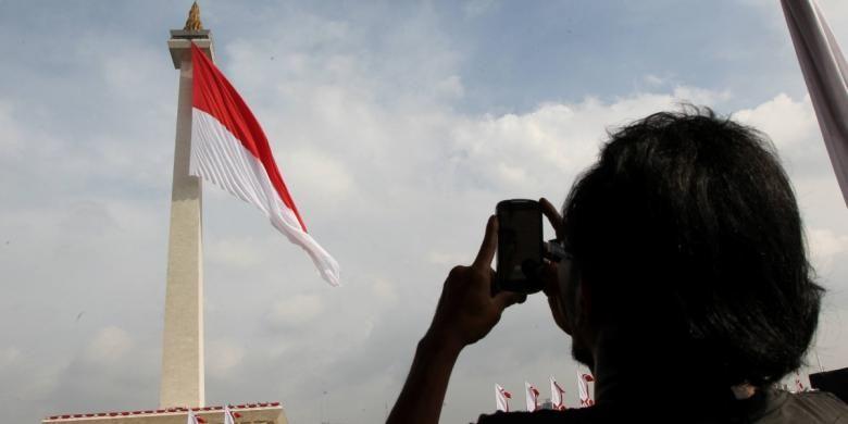 Bendera Merah Putih raksasa dikibarkan oleh anggota TNI dan anggota Pramuka di Tugu Monas, Jakarta, Jumat (19/12/2014). Pengibaran bendera Merah Putih tersebut merupakan puncak peringatan Hari Bela Negara sekaligus tercatat dalam rekor dunia dengan kategori bendera terbesar di dunia dengan ukuran 2.250 meter persegi.