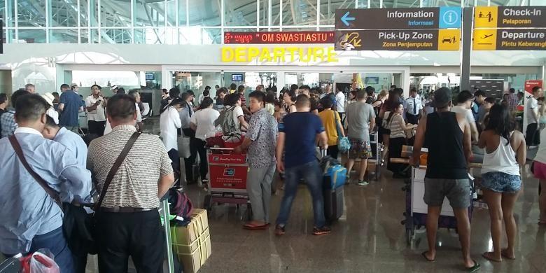 Calon penumpang sedang check in di terminal internasional Bandara Ngurah Rai.