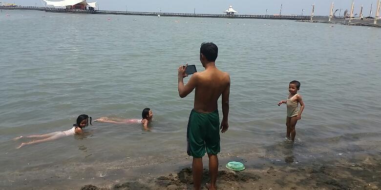 Sejumlah warga tampak asyik berenang di Pantai Ancol, Jakarta Utara pada Selasa (1/12/2015)