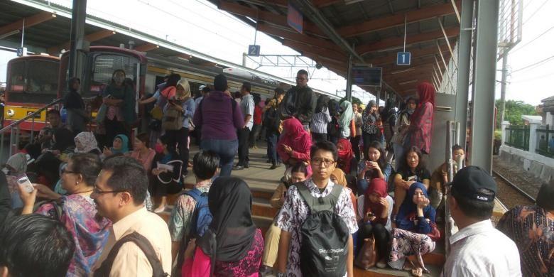 Para calon penumpang KRL commuter line di Stasiun Depok yang memilih duduk di atas tangga peron akibat rangkaian KRL yang tersedia tak kunjung diberangkatkan, Rabu (3/2/2016).