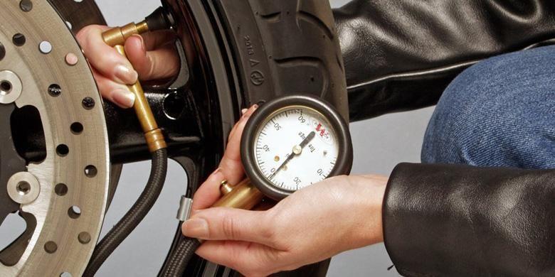 Mengukur tekanan ban.