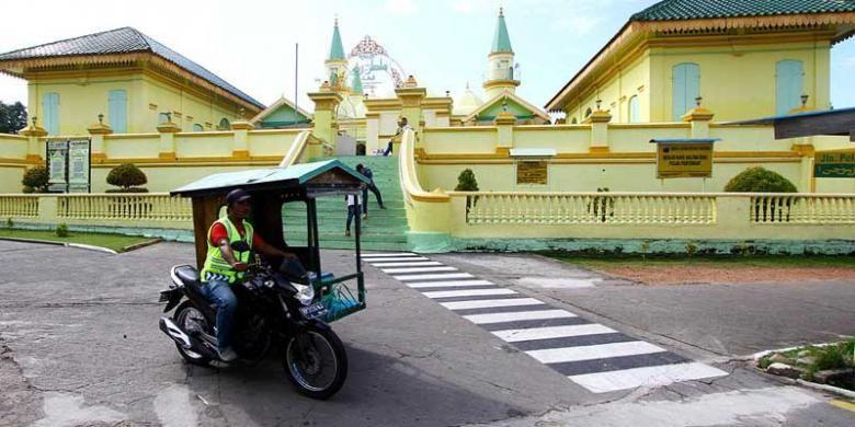 Becak motor melintas di Masjid Raya Sultan Riau atau dikenal sebagai Masjid Penyengat di Tanjung Pinang, Kepulauan Riau. Untuk berkeliling Pulau Penyengat, alternatif transportasi utama adalah becak motor.
