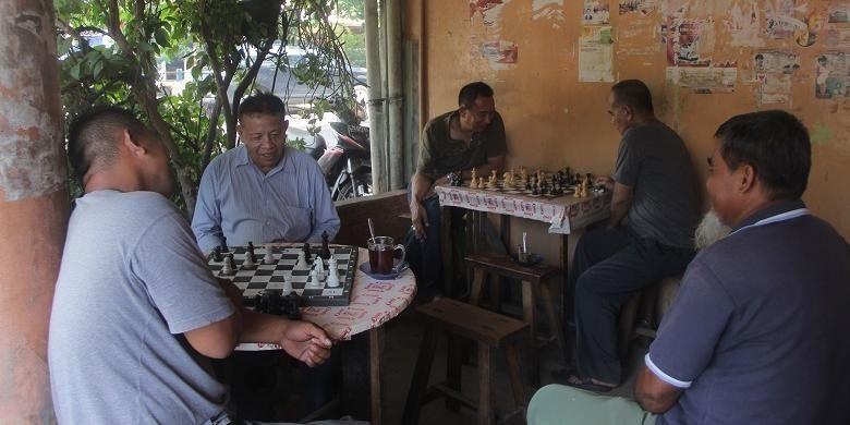 Pengunjung menikmati kopi sambil bermain catur di Warung Kopi Kong Djie, Belitung, Kamis (10/3/2016).