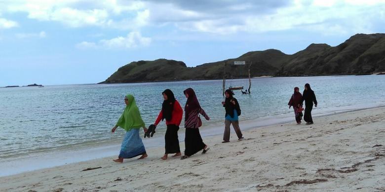 Beberapa wisatawan berjalan di Pantai Tanjung Aan, Lombok Tengah, Nusa Tenggara Barat.