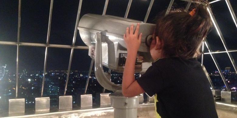 Tampak sejumlah pengunjung menikmati pemandangan di pelataran puncak Monas, Selasa (5/4/2016) malam. Untuk pertama kalinya, Monas membuka wisata malam ke puncaknya hingga pukul 22.00 WIB.