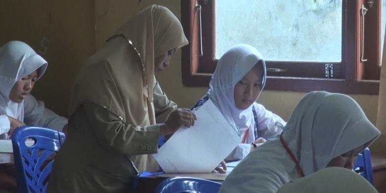 Seorang guru pengawas temgah menjelaskan soal kepada siswa yang ikut ujian