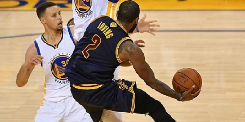 Stephen Curry mencoba menjaga pergerakan Kyrie Irving saat Golden State Warrios menjamu Cleveland Cavaliers di Oakland pada final NBA, Minggu (5/6/2016).