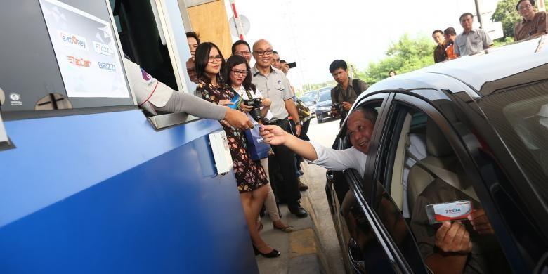 Kepala BPJT Herry Trisaputra Zuna disaksikan Wakil Direktur Utama LMS Hudaya Arryanto (kedua dari kanan) menerima kartu tol setelah diberlakukan uji coba sistem integrasi pembayaran tol di Gerbang Tol Palimanan, Tol Cikopo-Palimanan, Senin (13/6/2016).