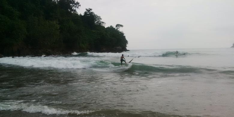 Wisatawan mancanegara berselancar di Pantai Wedi Awu, Malang, Jawa Timur, Minggu (12/6/2016).