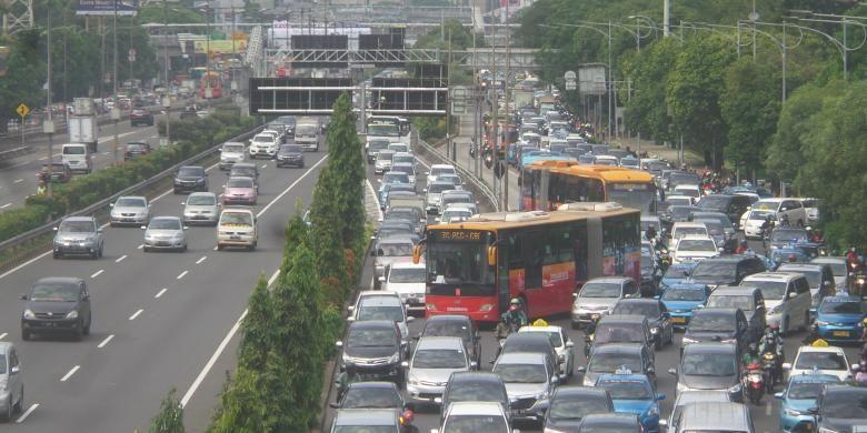 Antrian kendaraan roda empat yang hendak keluar dari Tol Dalam Kota dari pintu tol Semanggi, Selasa (21/6/2016). Terlihat kondisi ini membuat perjalanan bus transjakarta menjadi tersendat.