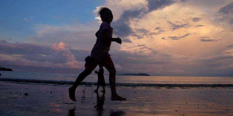 Anak-anak Desa Barawai bermain di pantai saat matahari mulai tenggelam.