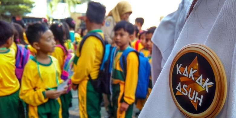 Mengenakan selendang songket dan PIN, kakak asuh SDN 2 Cakranegara menemani murid baru di hari pertama sekolah.