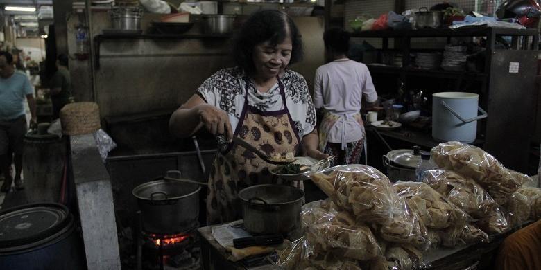 Penjual nasi tumpang, Harini (62) menyajikan nasi tumpang di Pasar Gede Hardjonagoro, Solo, Jawa Tengah, Jumat (22/7/2016). Nasi tumpang merupakan kombinasi olahan tempe busuk, tahu, dan daun bayam rebus.
