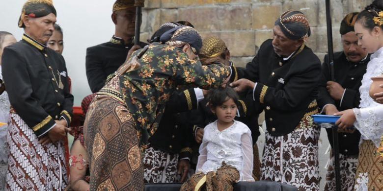 Prosesi pemotongan rambul gimbal oleh Staf Ahli Bidang Multikultural Kemenpar, Harry Untoro di Candi Arjuna, Dieng, Minggu (7/8/2016).