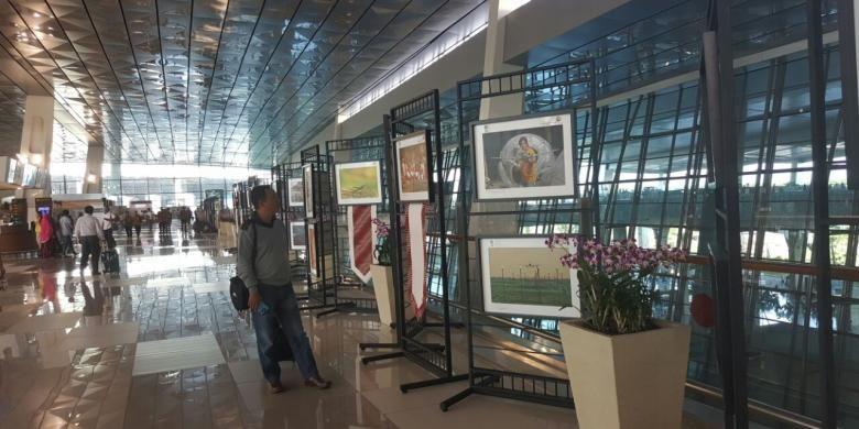 Calon penumpang melihat hasil karya di pameran foto dekat area kedatangan Terminal 3 New Bandara Soekarno-Hatta, Tangerang, Rabu (31/8/2016).