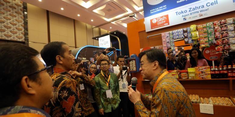 Direktur Utama PT Bank Tabungan Pensiunan Nasional Tbk Jerry Ng tengah menjelaskan tentang BTPN Wow kepada Presiden Joko Widodo pada acara Indonesia Fintech Festival & Conference.