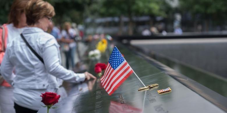 Para pengunjung menyentuh nama-nama korban tewas dalam serangan terhadap gedung World Trade Center di New York, AS, 11 September 2001 pada peringatan 15 tahun serangan teror itu, Minggu (11/9/2016). Pada 11 September 2017, mereka peringati 16 tahun serangan itu.