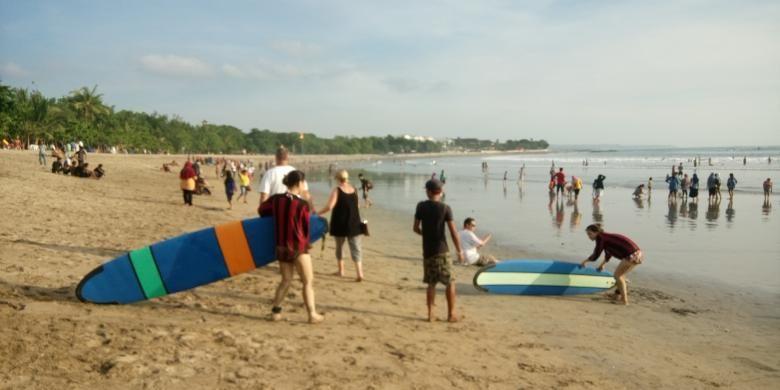 Wisatawan surfing di Pantai Kuta
