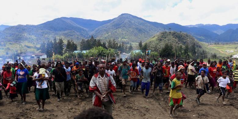 Warga bersama-sama memasuki lapangan Trikora untuk memulai acara adat bakar batu di Lapangan Trikora Distrik Ilaga, Kabupaten Puncak, Papua, Kamis (15/9/2016). Tradisi bakar batu merupakan salah satu tradisi terpenting di Papua yang berfungsi sebagai tanda rasa syukur, menyambut tamu, atau acara perdamaian setelah perang antar suku.