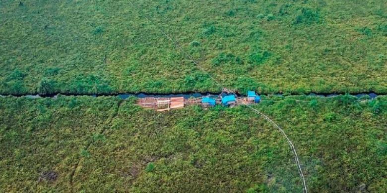 Salah satu kawasan hutan konservasi Cagar Biosfer Giam Siak Kecil dan Bukit Batu Riau yang sudah terbuka akibat pembalakan dan perambahan. Tampak salah satu pondok pembalak liar beserta kayu olahan di samping kanal yang membelah kawasan cagar biosfer. Foto diambil pada Rabu (5/10/2016).