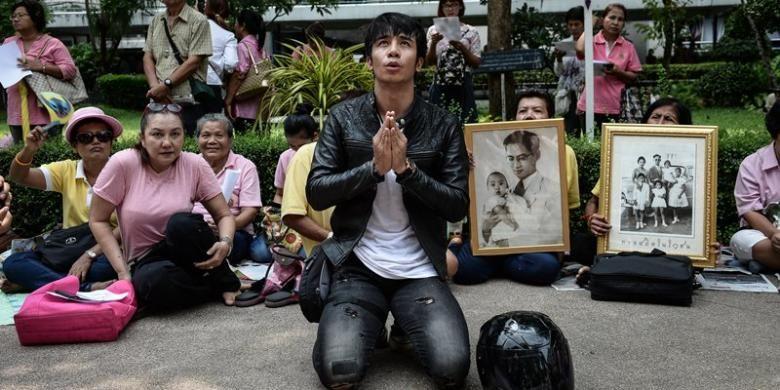 Seroang pria berlutut dan berdoa di depan RS Siriraj, Bangkok tempat Raja Bhumibol Adulyadej dirawat, Kamis (13/10/2016).