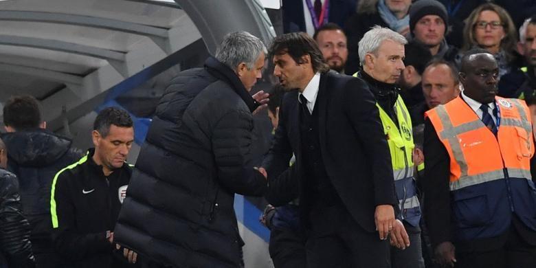 Manajer Manchester United, Jose Mourinho, membisikkan sesuatu kepada koleganya di Chelsea, Antonio Conte, setelah duel kedua tim pada partai Premier League di Stadion Stamford Bridge, Minggu (23/10/2016).