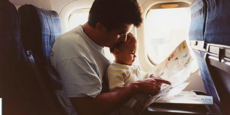 Ilustrasi penumpang memangku bayi di pesawat.