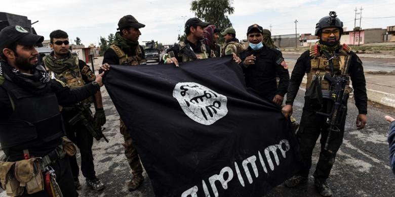 Tentara Irak memperlihatkan bendera ISIS yang diperoleh setelah mereka merebut pertahanan ISIS di sebuah desa di sisi timur kota Mosul.
