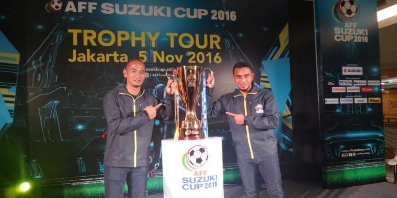 Eks penyerang timnas Indonesia, Kurniawan Dwi Yulianto (kiri), dan gelandang Sriwijaya FC, Firman Utina, berpose dengan trofi Piala AFF 2016 yang dipamerkan di kawasan fx Sudirman, Jakarta, 5 November 2016.