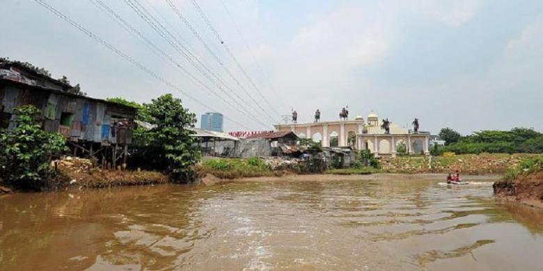 Bangunan semi permanen milik warga dan pintu gerbang salah satu komplek perumahan tampak di salah satu sisi bantaran Kali Angke di Kembangan, Jakarta Barat.
