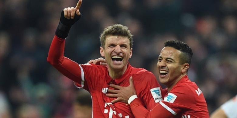 Thomas Mueller merayakan gol pertamanya musim ini bersama Thiago Alcantara saat Bayern Muenchen menang atas Wolfsburg di Allianz Arena, Sabtu (10/12/2016).