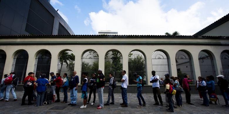 Warga kota Caracas, Venezuela rela antre berjam-jam di sebuah bank untuk menukar uang pecahan 100 bolivar yang akan dihapus pemerintah.