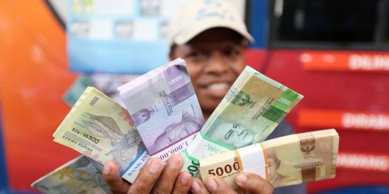 Warga menunjukkan mata uang rupiah Negara Kesatuan Republik Indonesia (NKRI) tahun emisi 2016 di lokasi penukaran uang di Blok M Square, Jakarta, Senin (19/12/2016). Bank Indonesia resmi meluncurkan uang NKRI tahun emisi 2016 dengan menampilkan 12 pahlawan nasional yakni 7 uang rupiah kertas dan dan 4 uang rupiah logam.