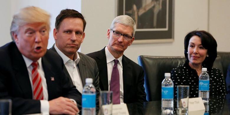 Presiden terpilih Amerika Serikat Donald Trump (paling kiri) berbicara sambil disaksikan oleh pendiri PayPal Peter Thiel (kedua dari kiri), CEO Oracle Safta Catz (paling kanan), dan CEO Apple Tim Cook dalam pertemuan dengan para petinggi perusahaan teknologi yang digelar di Trump Tower, New York, Rabu (14/12/2016) minggu lalu.