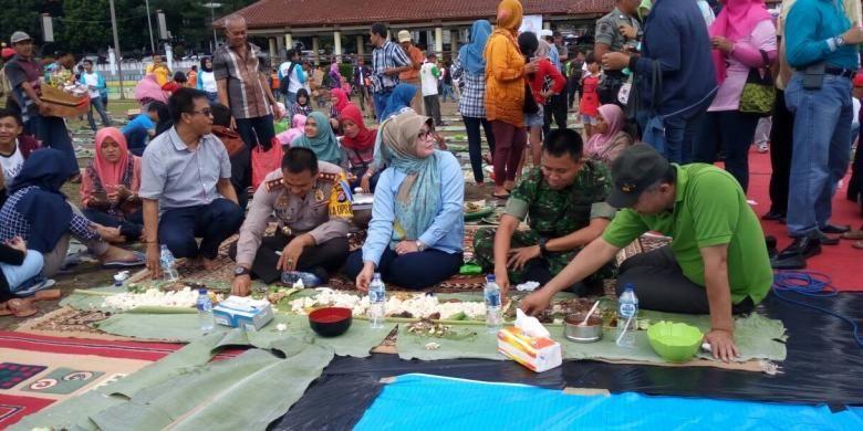 Bupati Pandeglang Irna Narulita (tengah) didampingi Kepala Kepolisian Resor Pandeglang Ajun Komisaris Besar Ary Satriyan, Komandan Kodim 0601/Pandeglang Letnan Kolonel Inf Ganiahardi, dan Ketua DPRD Pandeglang Gunawan menikmati hidangan di atas daun pisang di Alun-alun Pandeglang, Banten, Sabtu (31/12). Mereka bersama ratusan warga Pandeglang melakukan tradisi khas Pandeglang, yakni papahare atau membawa makanan untuk ditukar dan disantap bersama-sama.
