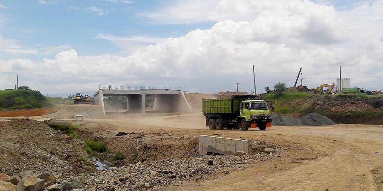 Sebuah truk tengah melintasi lokasi pembangunan Jalan Tol Soreang-Pasir Koja di Kecamatan Soreang, Kabupaten Bandung, Selasa (10/1/2016). Jalan tol sepanjang 10,57 kilometer ini direncanakan akan beroperasi Mei 2017.