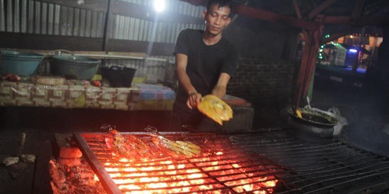 Pekerja membakar ikan di Warung Awak Awai 2, Jalan T Nyak Arief, Simpang Mesra, Banda Aceh, Senin (30/1/2017) malam.