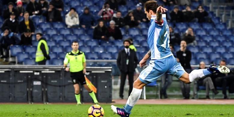 Gelandang Lazio asal Argentina, Lucas Biglia, melakukan tendangan penalti dan mencetak gol ke gawang AC Milan dalam pertandingan Serie A di Stadion Olimpico, Roma, Senin (13/2/2017).