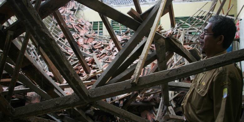 Guru Sekolah Dasar Negeri 2 Ciwaringin, Kecamatan Babakan, Kabupaten Cirebon, Selasa (21/2/2017), melihat bangunan sekolah yang ambruk sejak sebulan lalu. Siswa kelas I dan II di sekolah itu terpaksa mengungsi belajar di madrasah karena kelas mereka ambruk.