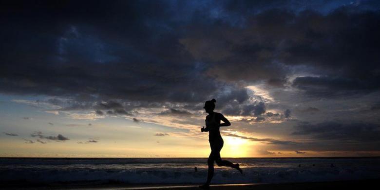 Seorang pelancong jogging di tepi pantai seiring terbenamnya matahari di anak-anak bermain-main di pantai saat senja di Seminyak, Bali, Sabtu (18/2/2017).