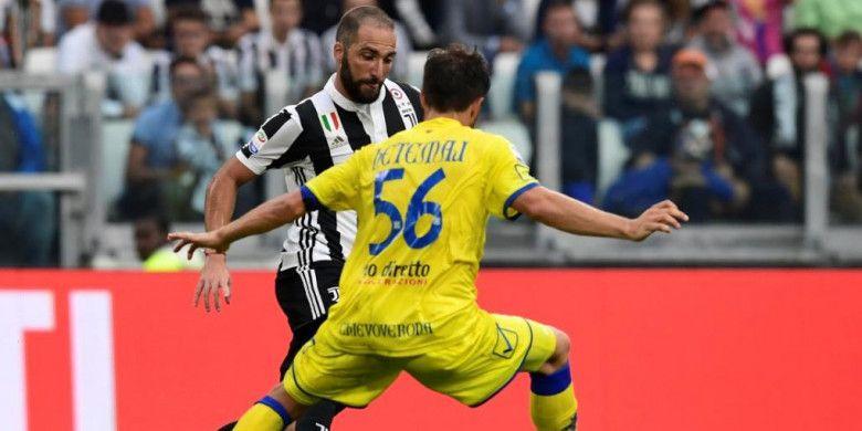 Striker Juventus, Gonzalo Higuain, mengecoh pemain Chievo, Perparim Hetemaj, dalam partai Liga Italia di Allianz Stadium, Turin, 9 September 2017.