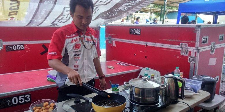 Salah satu anggota tim Honda memasak bahan makanan untuk tim dan ofisial AHRT di Sirkuit Madras, Chennai, India, Minggu (24/9/2017).