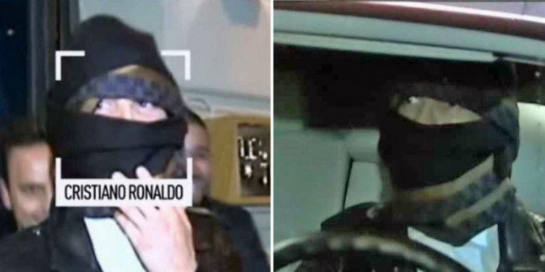 Cristiano Ronaldo menutupi wajahnya saat keluar dari sebuah restoran di kota Madrid.