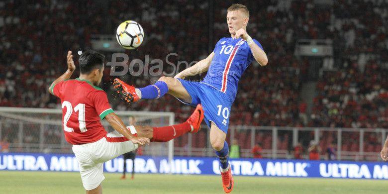 Pemain timnas Indonesia, Andik Vermansah, berduel dengan pemain timnas Islandia, Albert Gudmundsson, pada laga uji coba internasional di Stadion Utama GBK, Jakarta Selatan, Minggu (14/1/2018) malam.